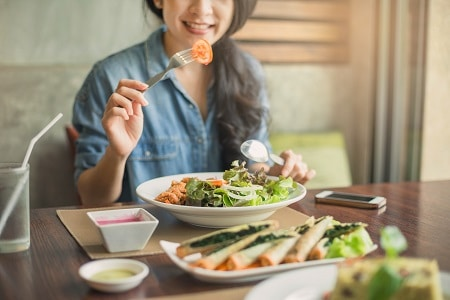 Young and happy woman eating healthy salad